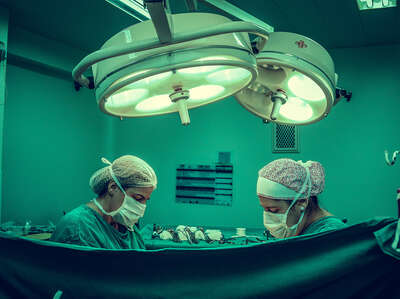 Two person doing surgery inside room 1250655