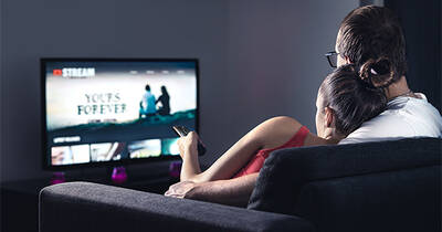 Couple sitting on couch streaming movies